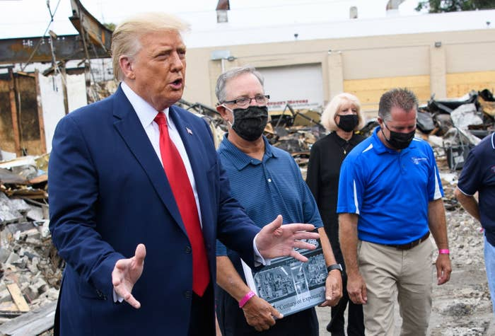 Trump talks while standing with people wearing facemasks near the remains of a building