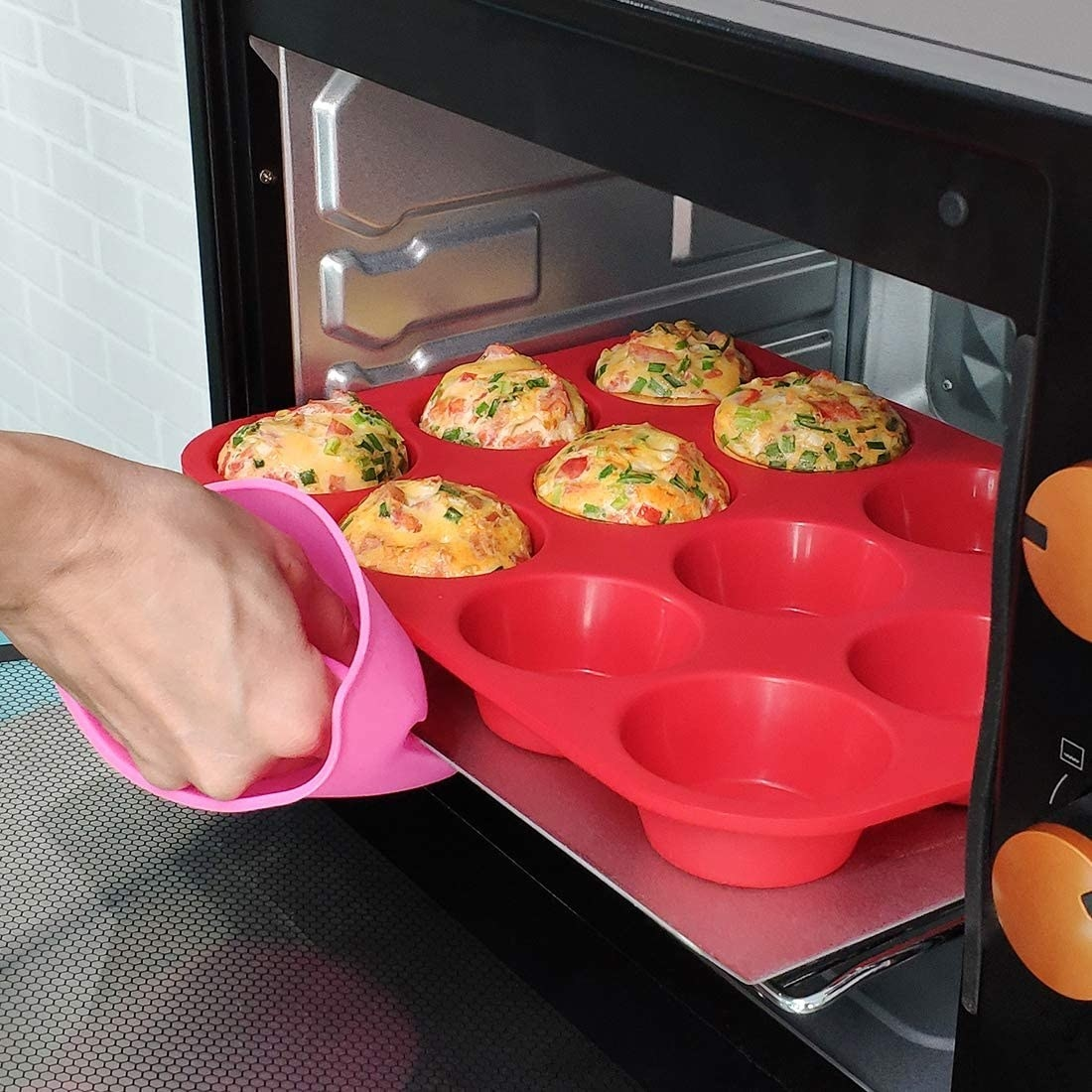 A person taking the silicone pan filled with egg muffins out of a toaster oven