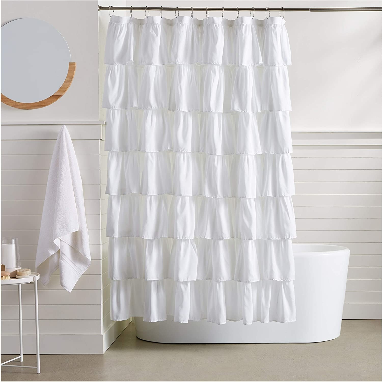 A ruffled shower curtain in front of a bathtub