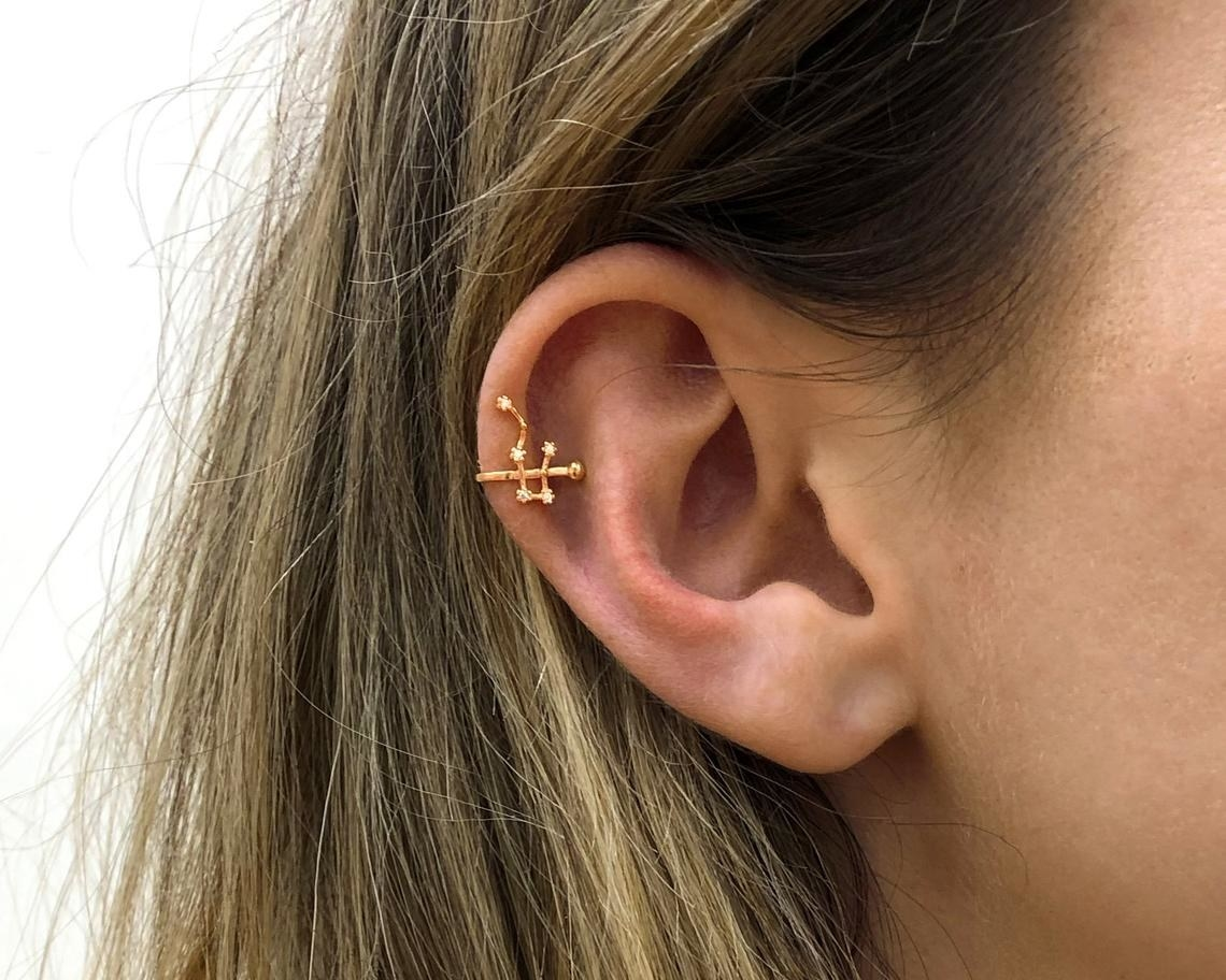 A person wearing a constellation ear cuff on their upper ear