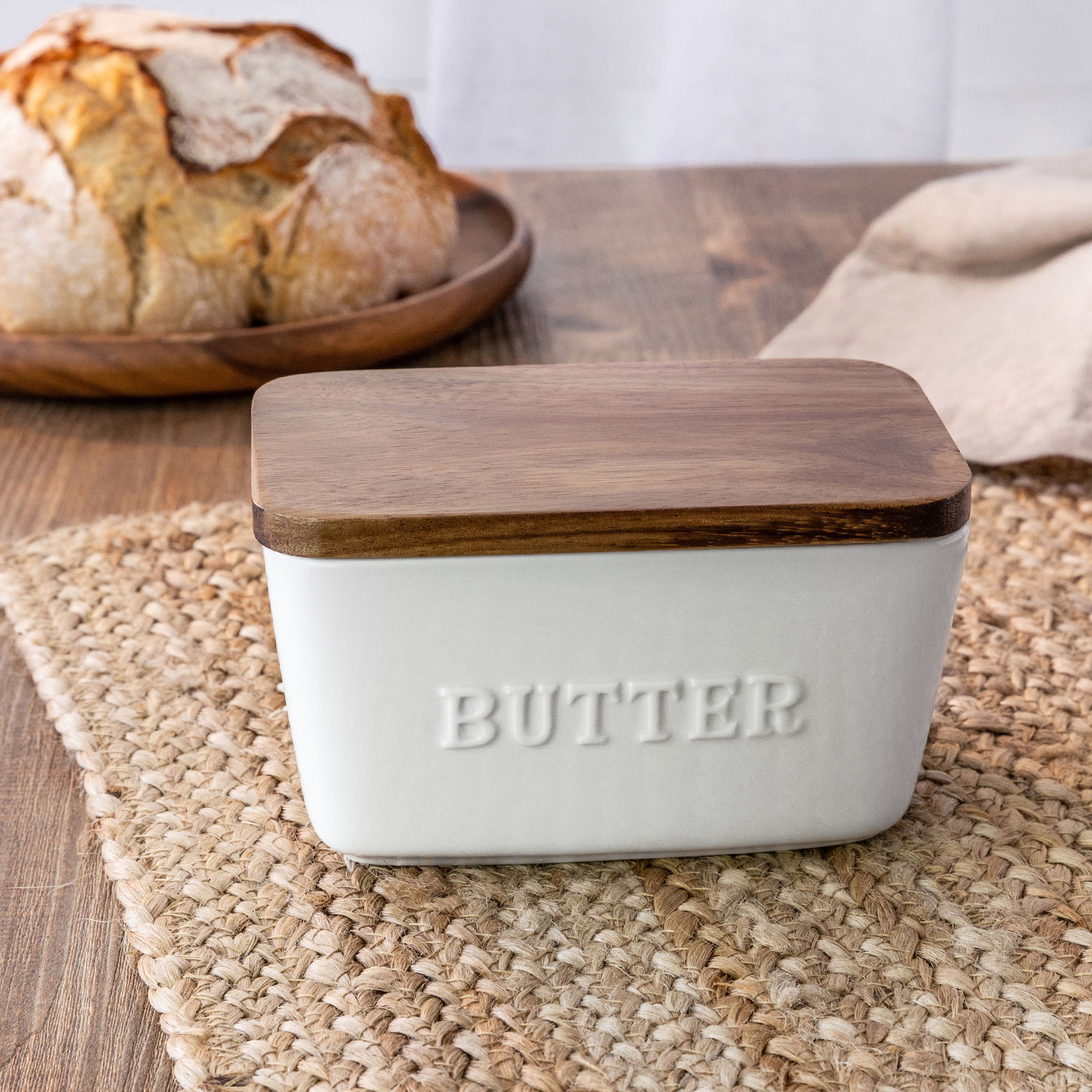 "White porcelain butter dish with ""butter"" embossed on the side and a wooden top"