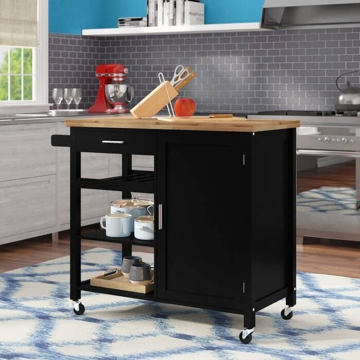 The Domenique Kitchen Cart Solid Wood storing pots and pans in a display kitchen