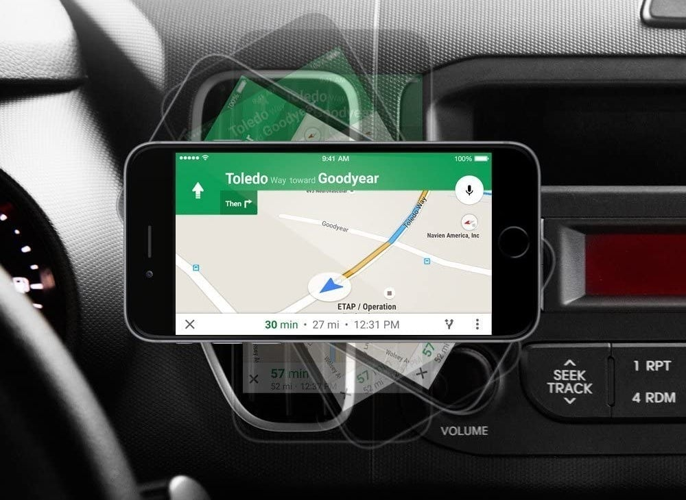 A phone shows navigation while mounted to a car