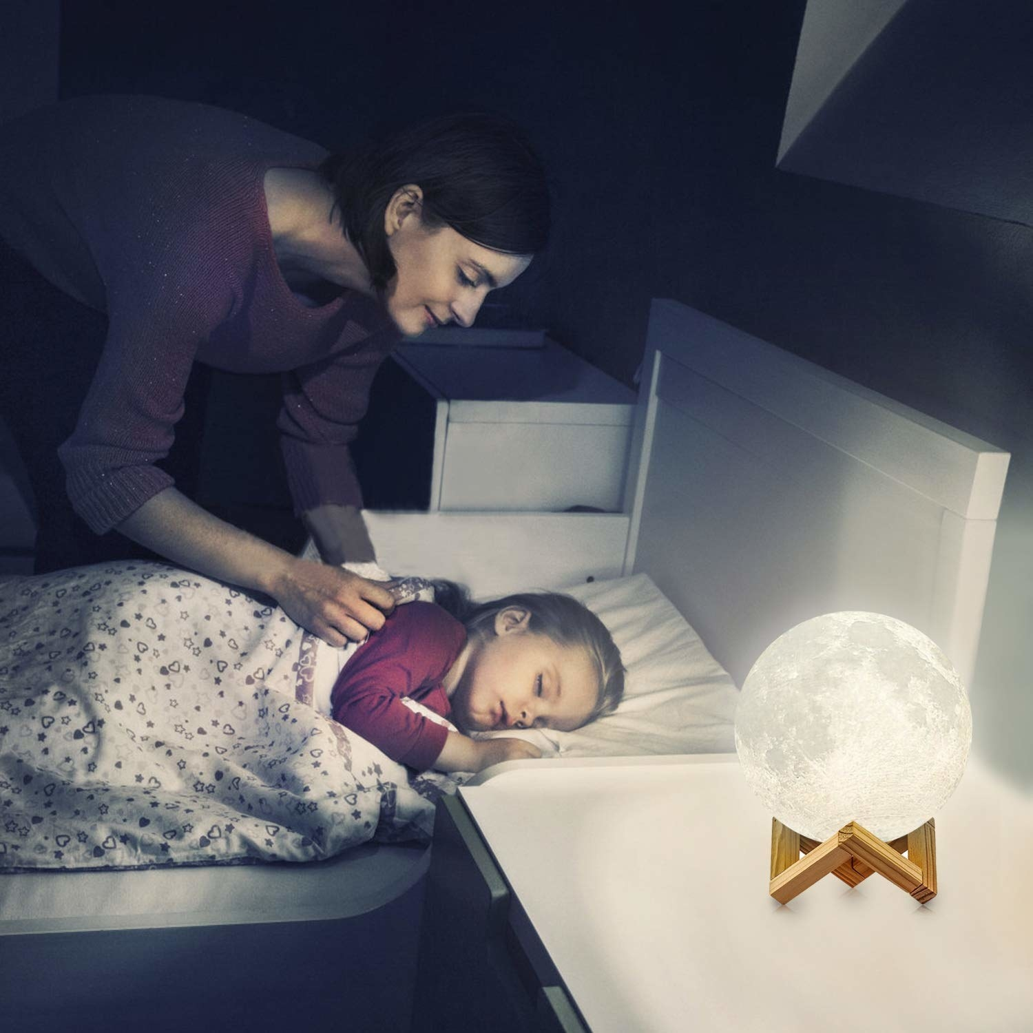 A mother putting the child to sleep with the moon lamp lit up on the bedside.