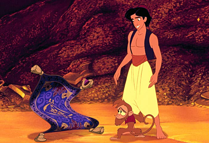 Aladdin standing next to Abu and his magical carpet