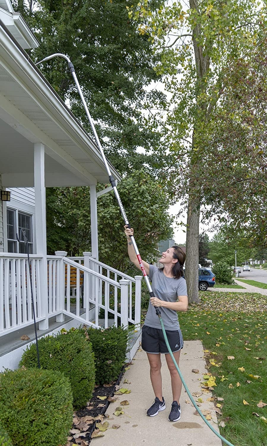 Model using the tool attached to a hose to clean gutters