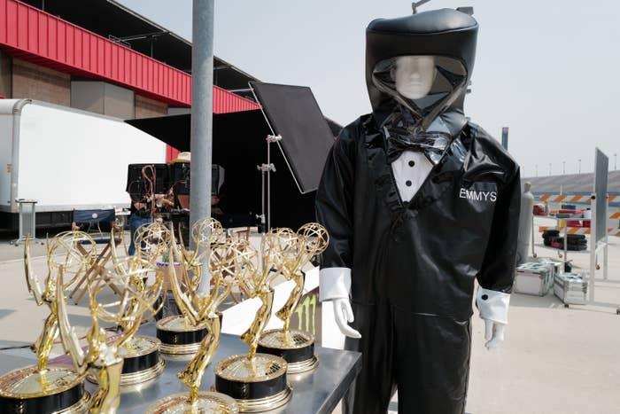 A mannequin in a hazmat suit next to Emmy trophies