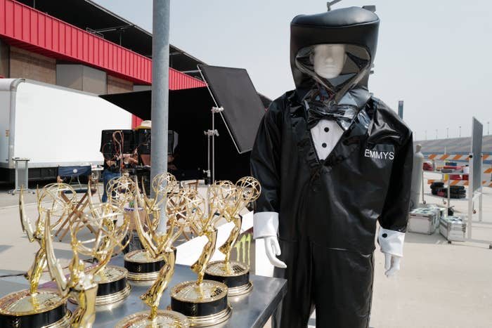 A mannequin in a hazmat suit next to Emmy trophies