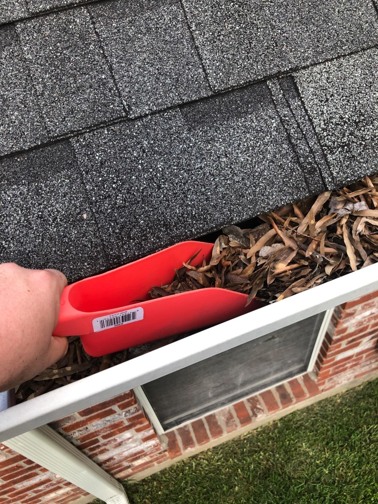 Reviewer using the red scoop to remove leaves from their gutter