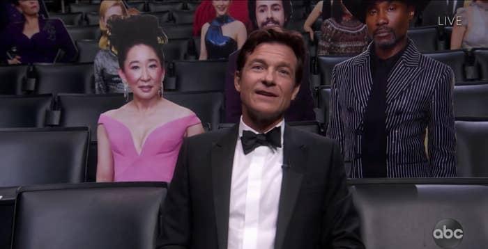 Jason sitting next to cutouts of celebrities