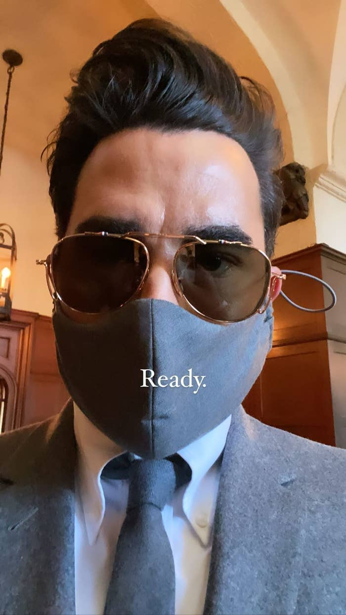 Dan Levy wearing a mask with his suit