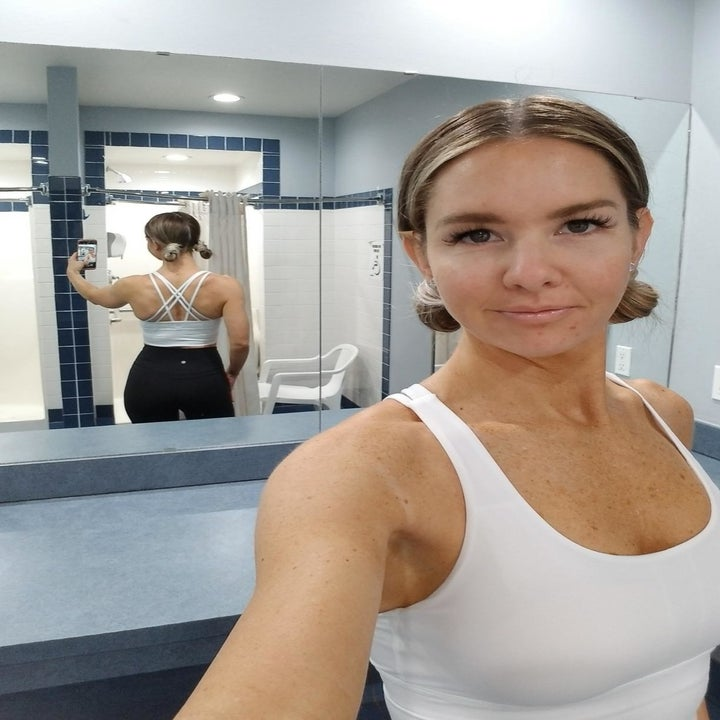 Reviewer wearing the sports bra taking a pic with their back to a mirror, showing the criss-cross pattern on the back