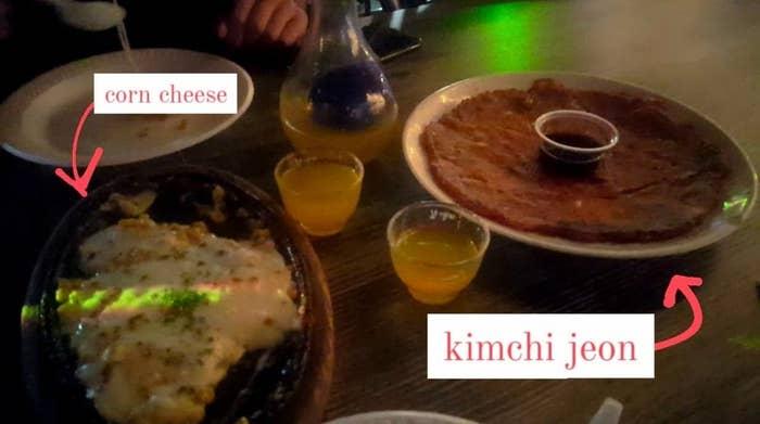 Corn cheese, kimchi jeon, and soju on a table at a Koreatown bar