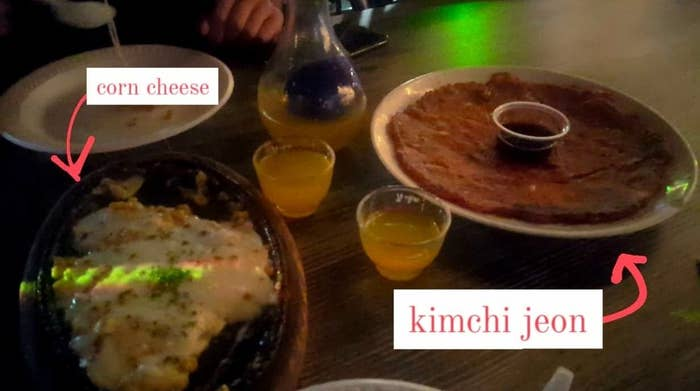 Corn cheese, kimchi jeon, and soju on a table at a Koreatown bar