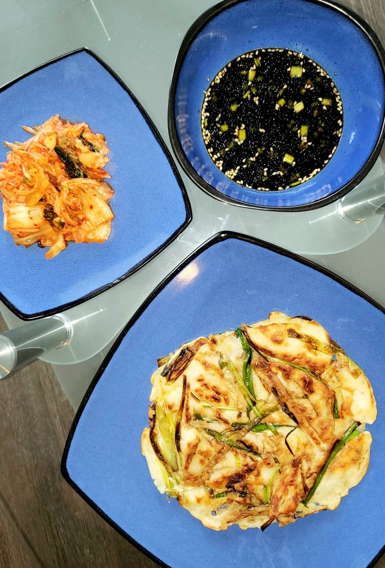 A top down view of the Korean pancake, a plate of kimchi, and the dipping sauce on a table
