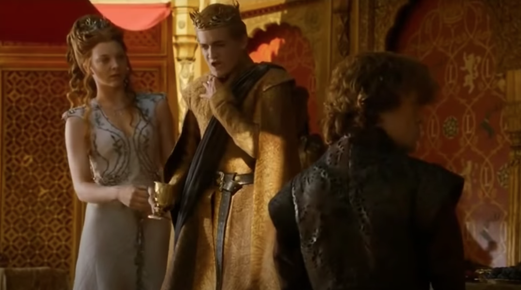 Still from Game of Thrones: Joffrey clasps his hand to his throat with a shocked look on his face