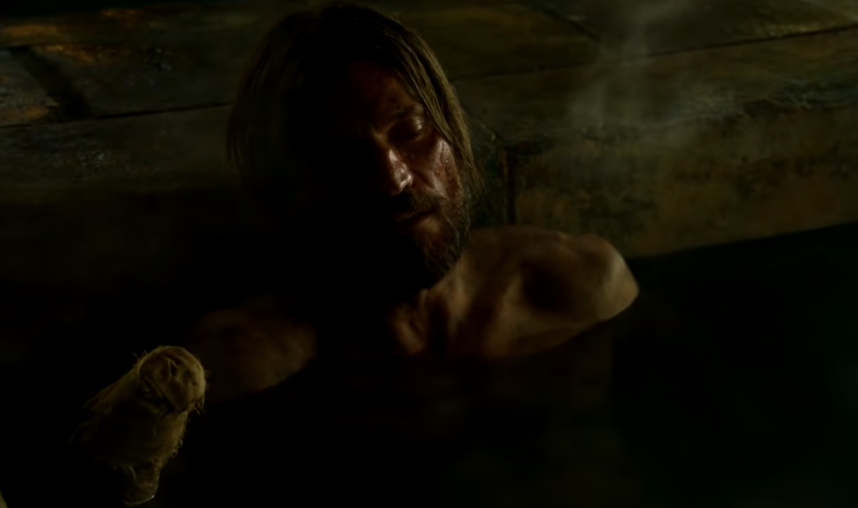 Still from Game of Thrones: a dirty and bloody Jaime Lannister sits in a bath, looking upset