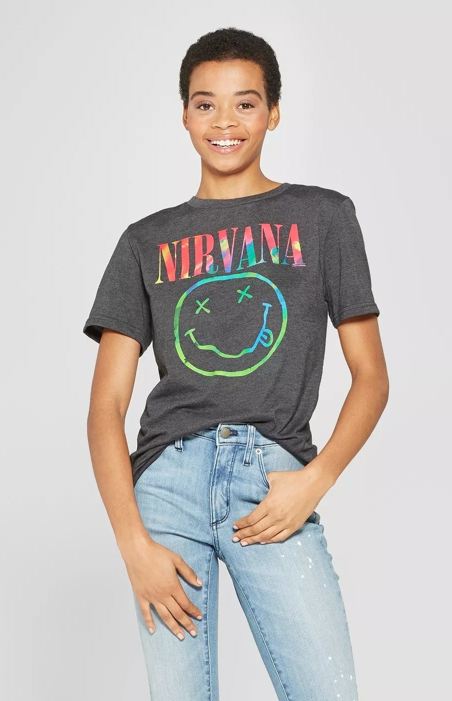 A model wearing a Nirvana T-shirt with a neon smile graphic