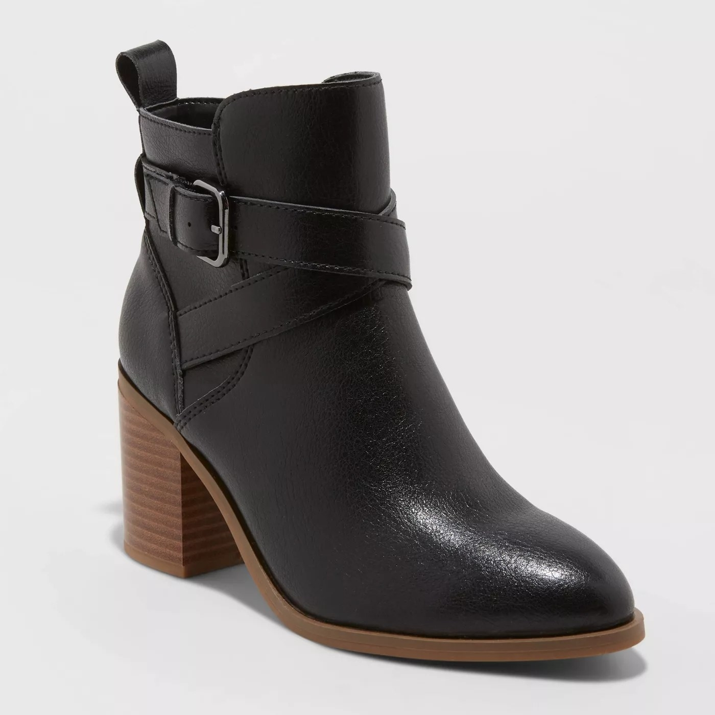 A black pair of ankle booties with brown heels and a cross-over buckle