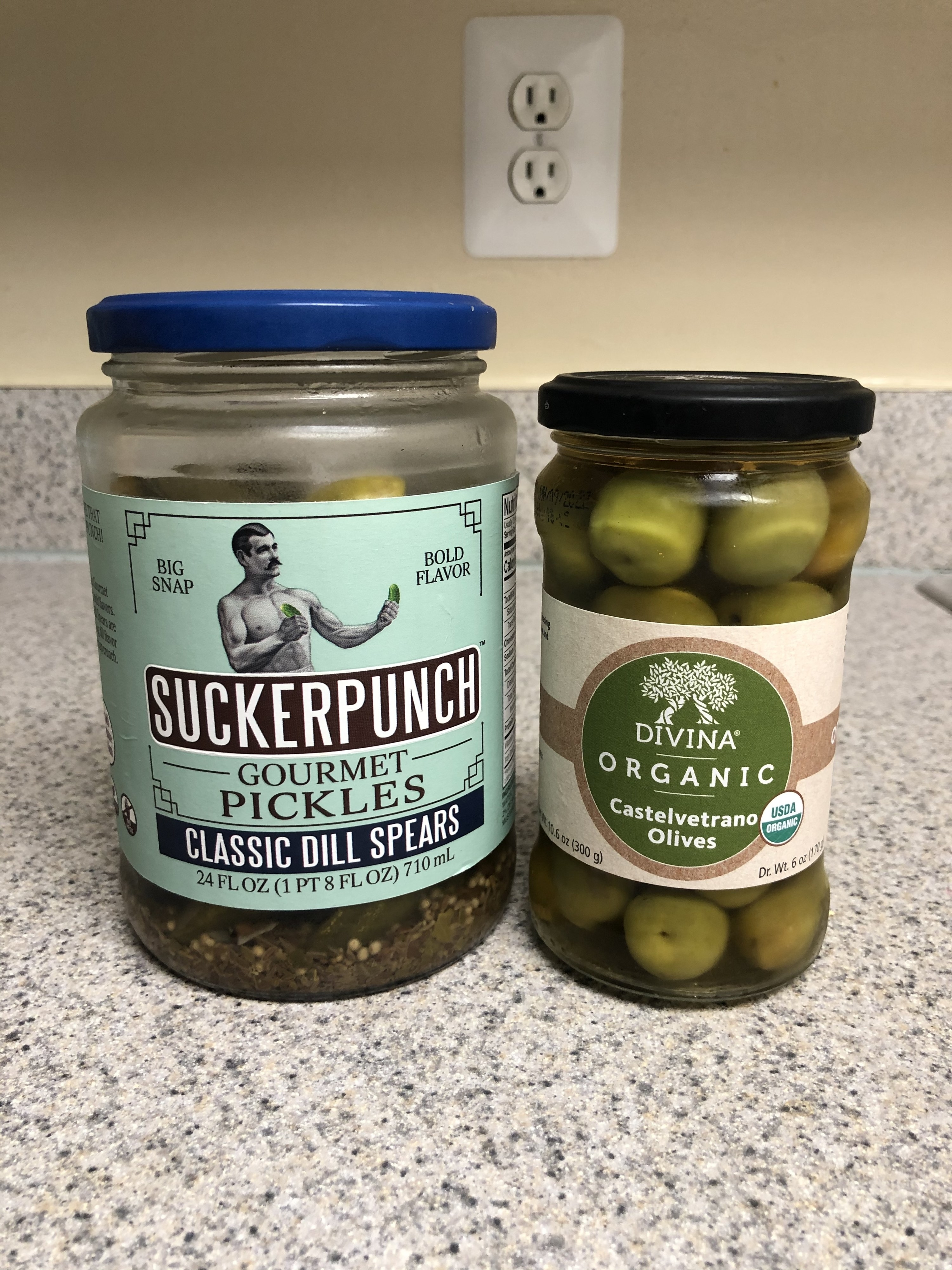 A jar of pickles next to a jar of green olives.