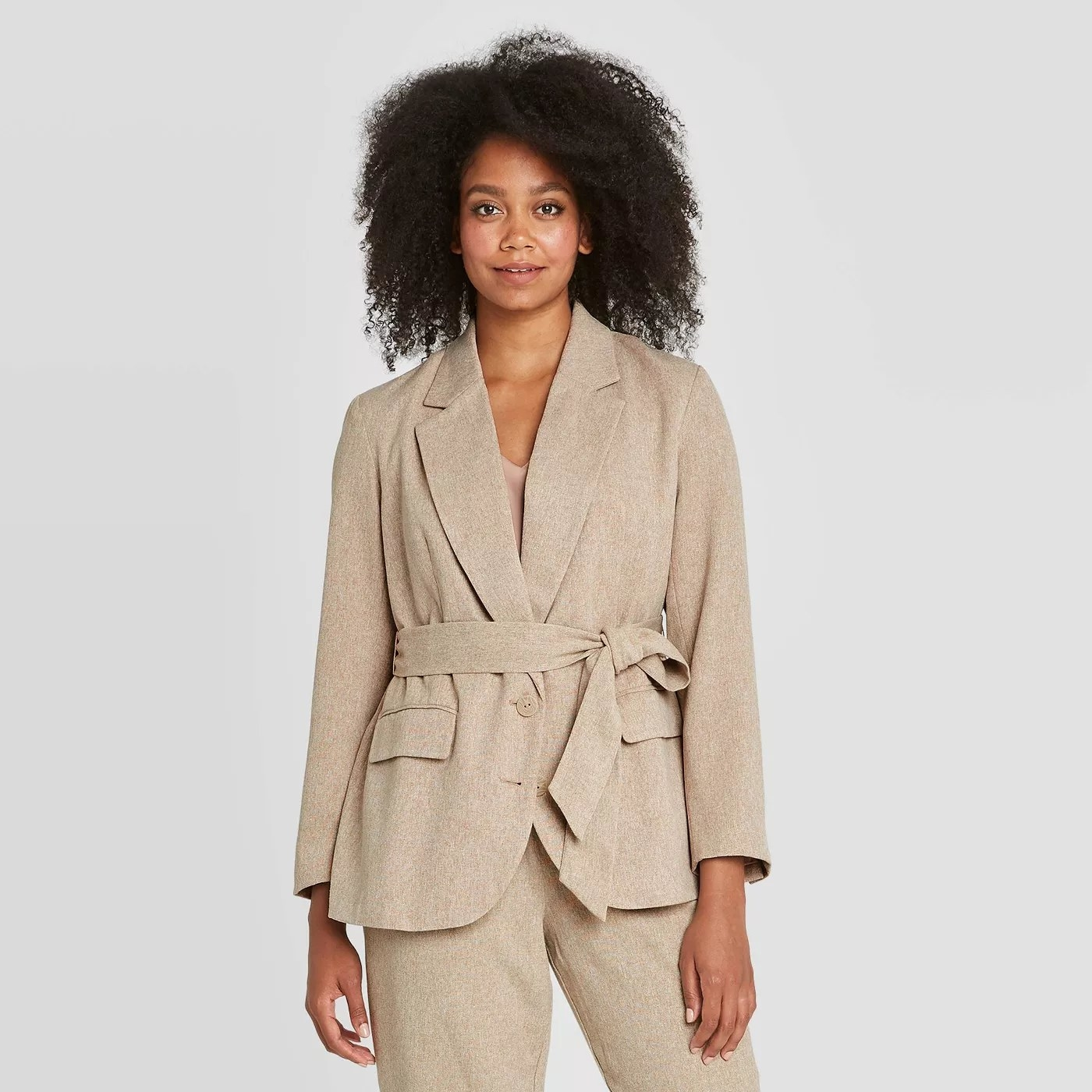 A model wearing a beige blazer with a belt, two buttons, and two pockets