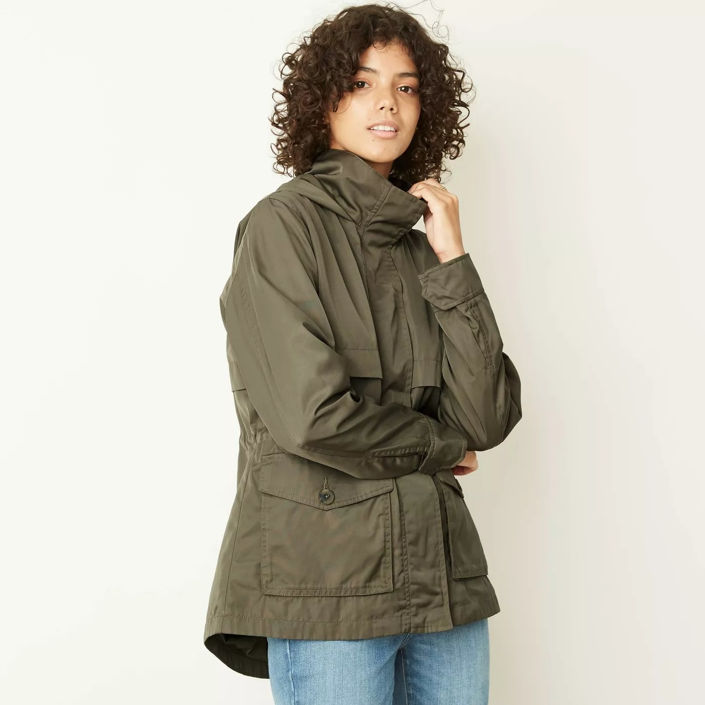A model wearing a zipped-up rain jacket with a high neck and large, buttoned pockets