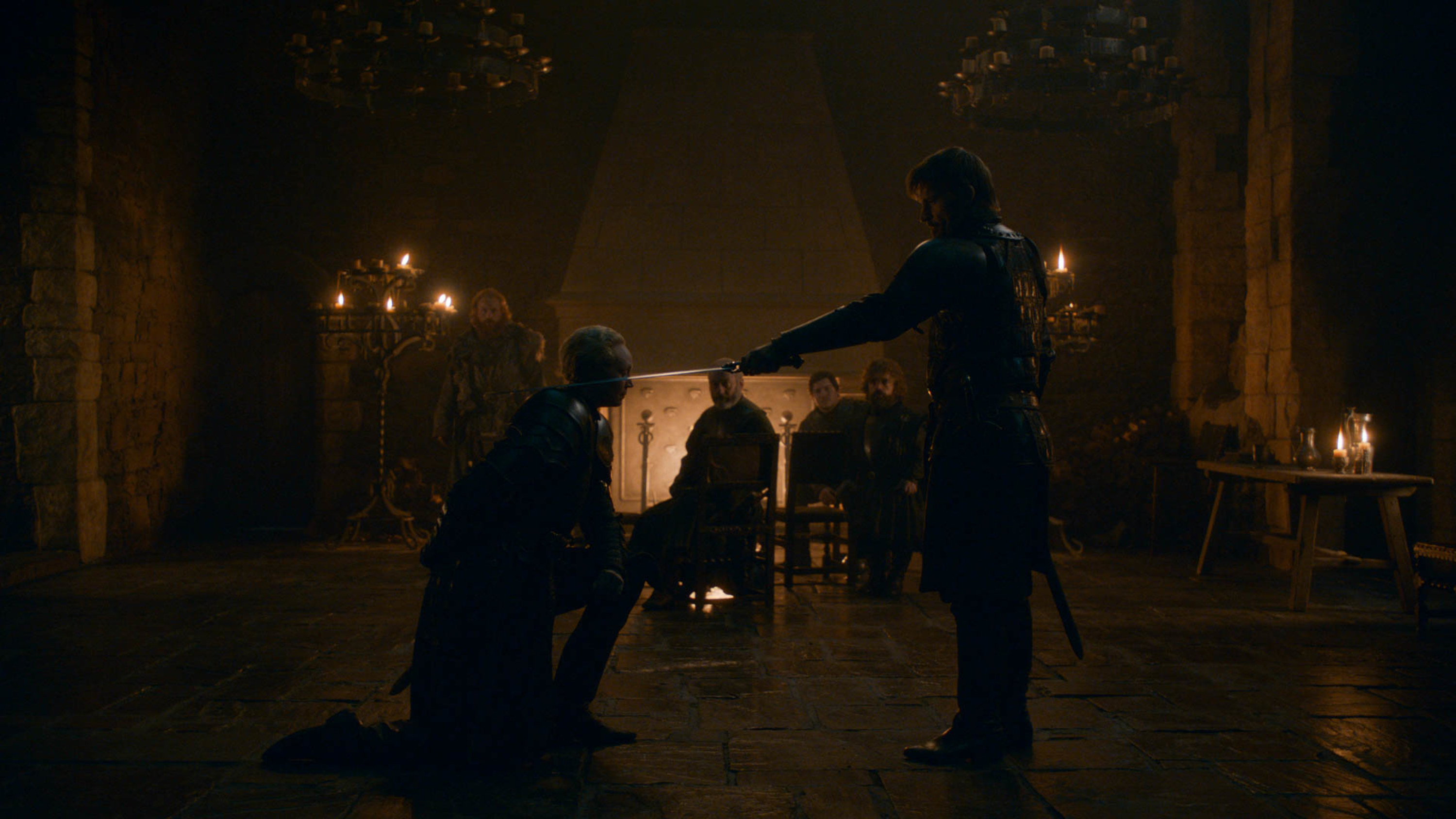Still from Game of Thrones: Brienne kneels before Jaime as he knights her with his sword; Davos, Tyrion, Tormund and Podrick look on in the background