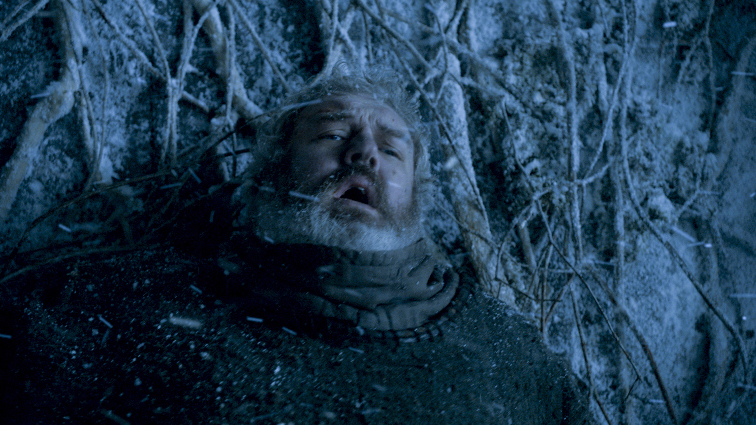 Still from Game of Thrones: Hodor stands against a tree-covered door looking pained