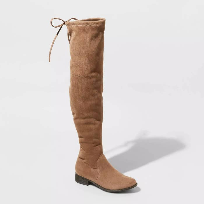 A taupe pair of microsuede, over-the-knee boots with a drawstring cord top