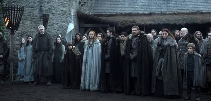 Still from Game of Thrones: The Stark family stand in a row in the courtyard at Winterfell