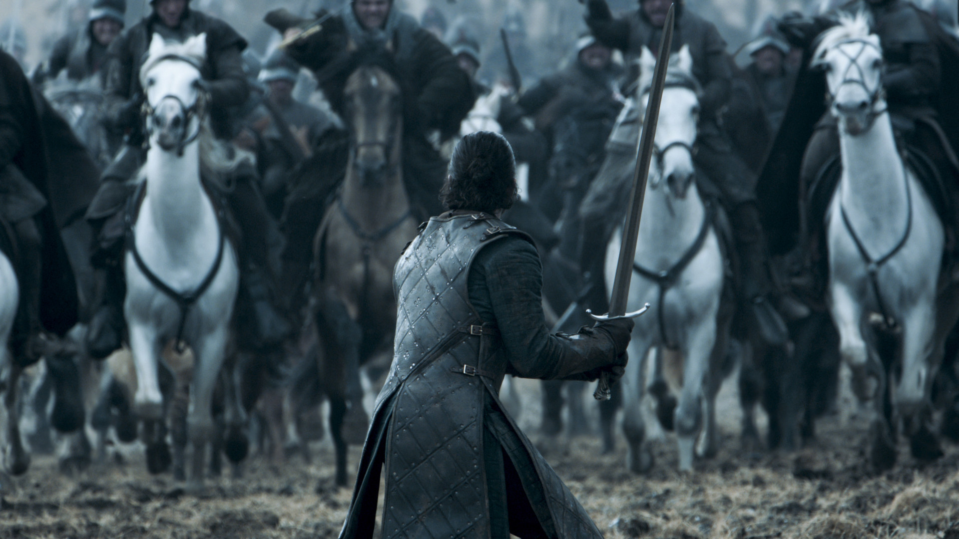 Still from Game of Thrones: Jon Snow stands with his back to the camera, holding a sword, as soldiers on horses charge towards him