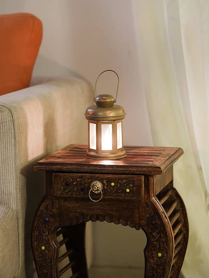 A golden lantern kept on a wooden bedside table.