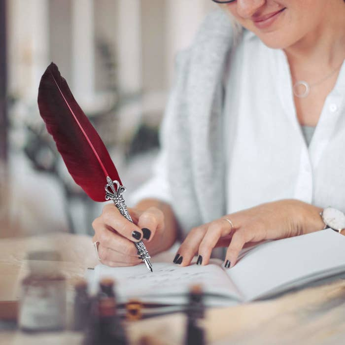 A woman writing on a notebook with a red-feathered quill pen.