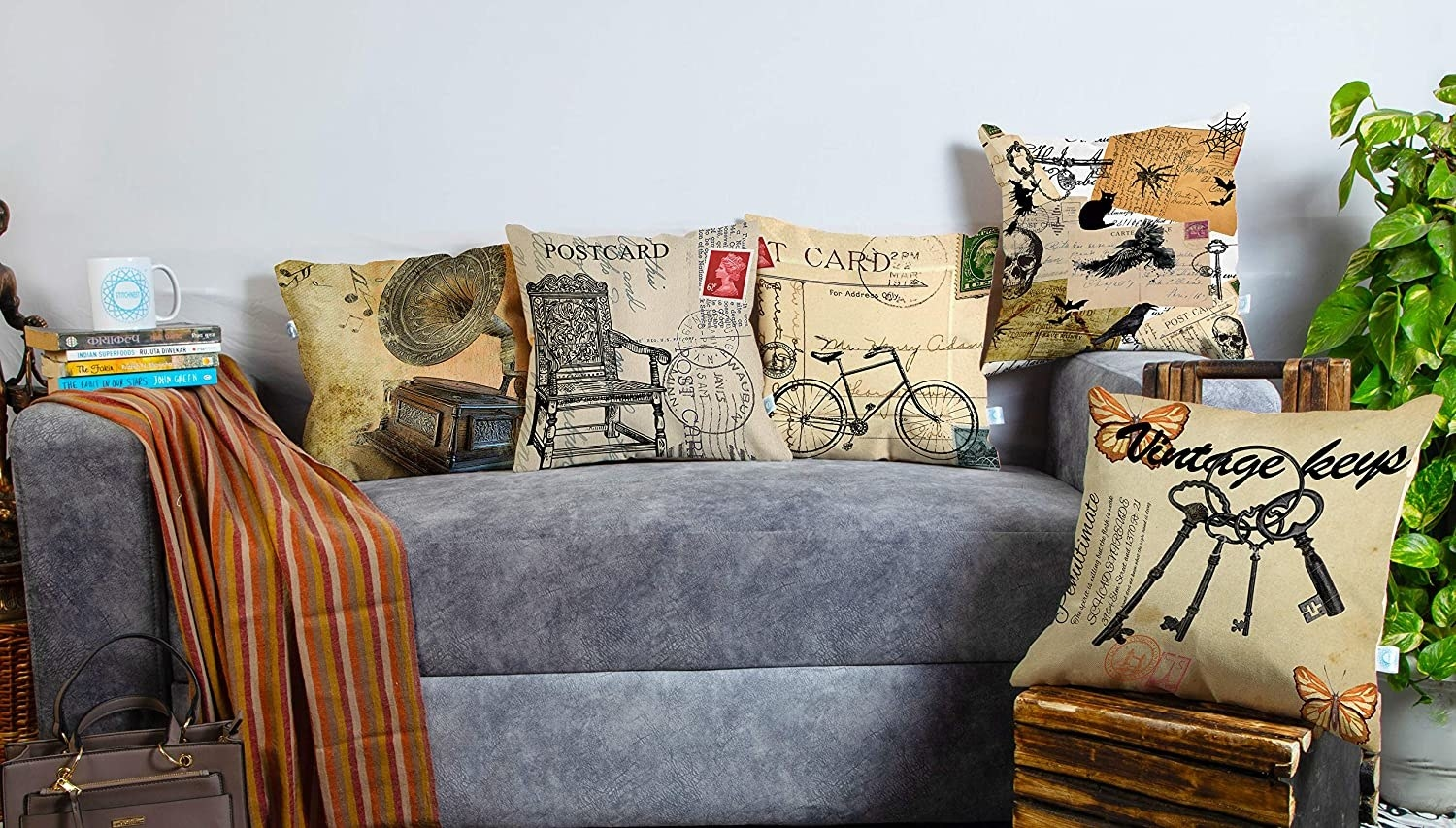 5 cushions with vintage-prints kept on a grey sofa.