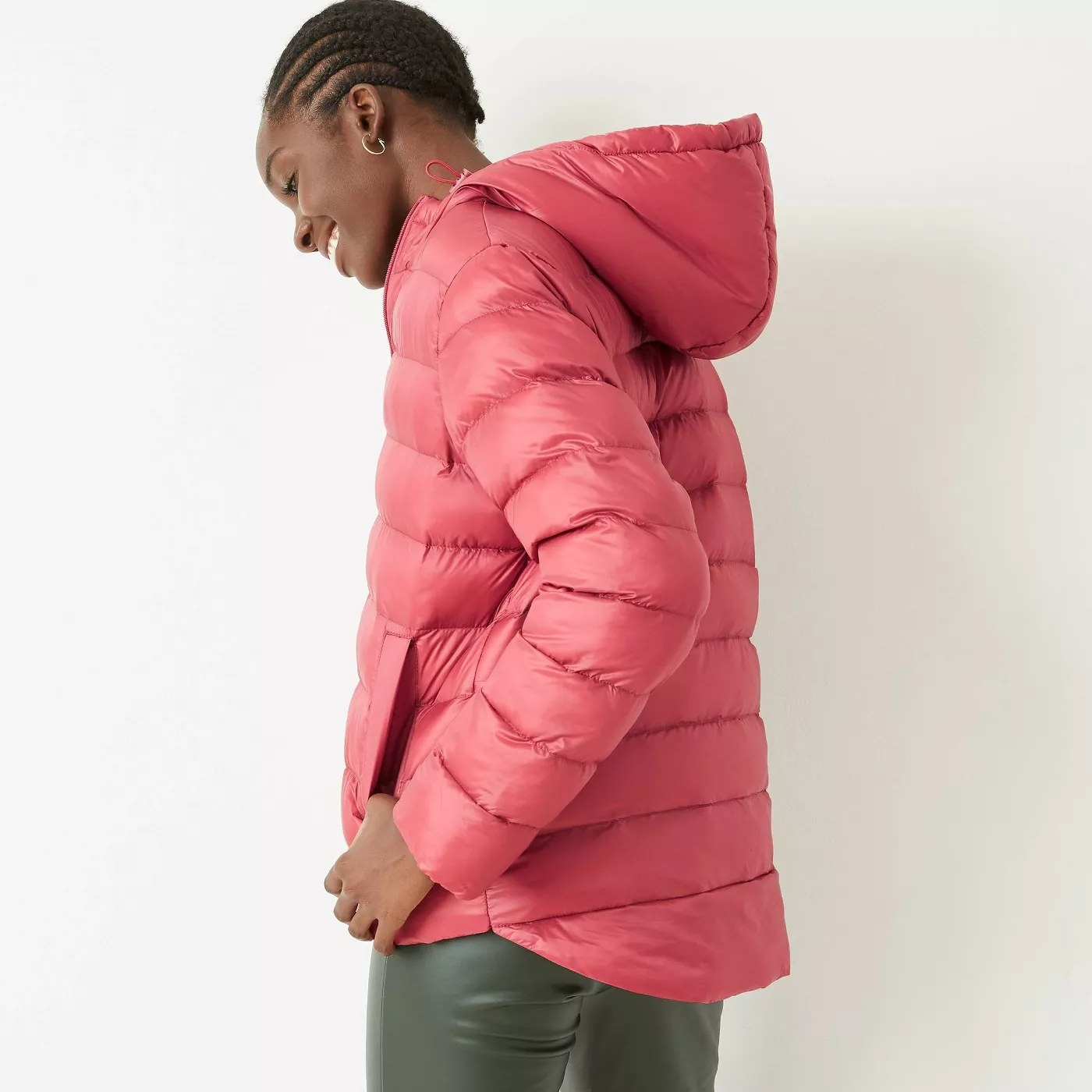 A model wearing a hooded, rose, puffer jacket