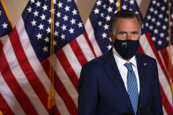Romney wears a face mask in front of several American flags
