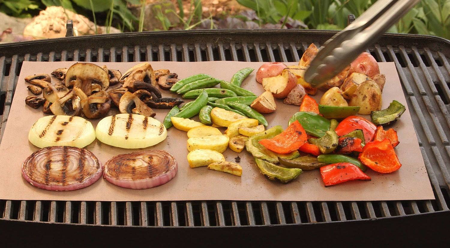 person grilling vetatables on a grill with yoshi copper grill mat on top