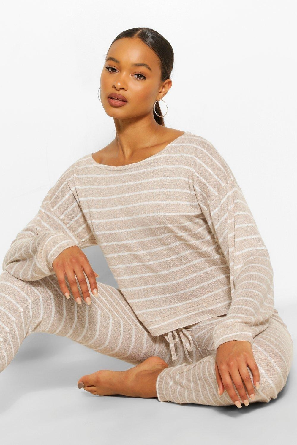 a model sitting cross legged in tan sweatpants with white vertical stripes and a matching sweatshirt