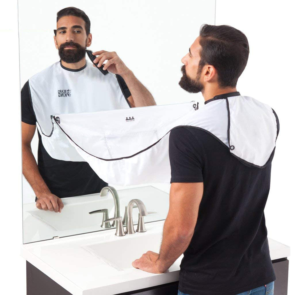 A person shaving their beard while wearing a large bib with the ends attached to the mirror