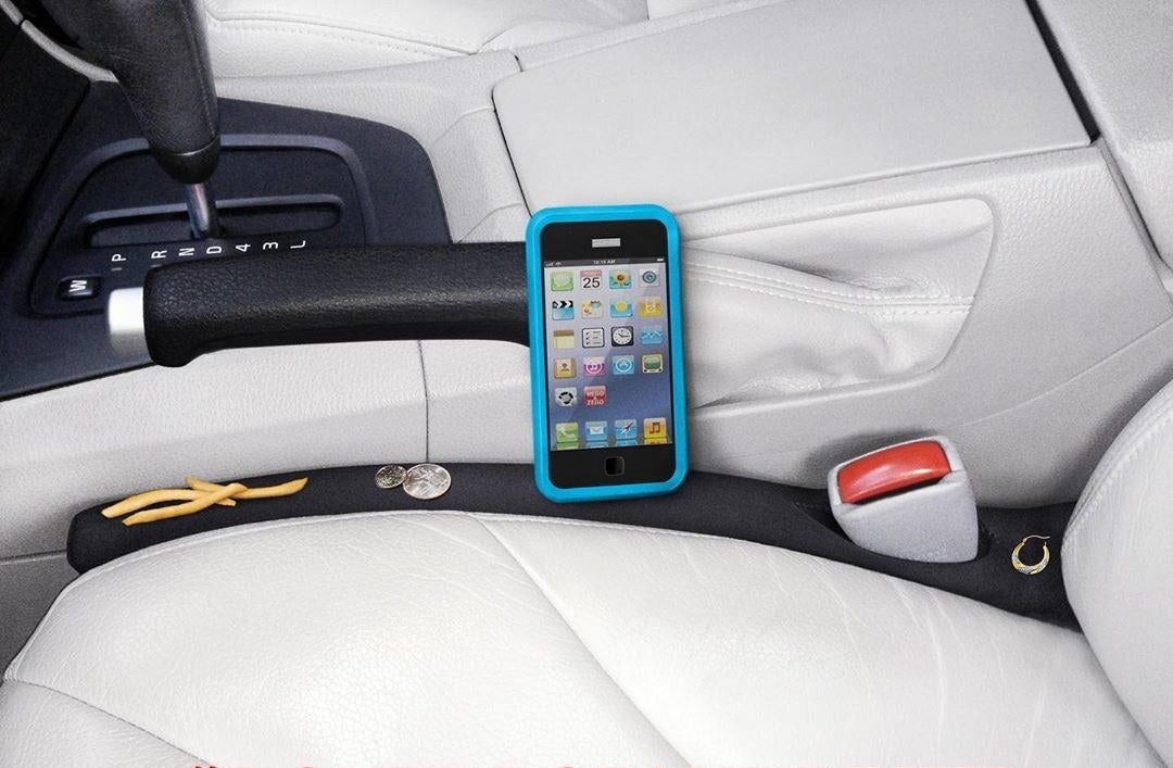 A long fabric block placed between a car seat and the console with fries, coins, and a phone on top of it