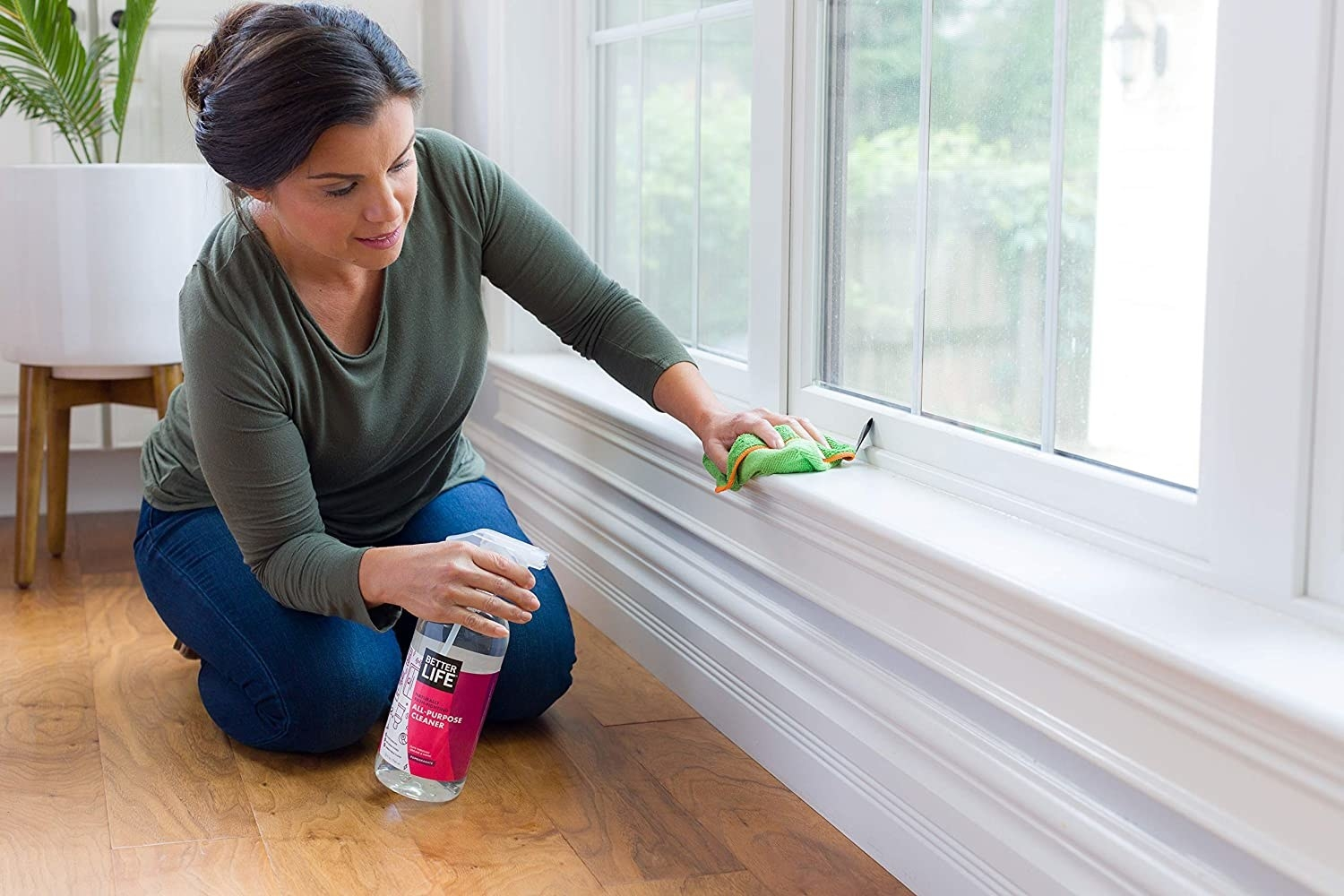 A person spraying the window ledge and baseboards with an all purpose cleaning solution