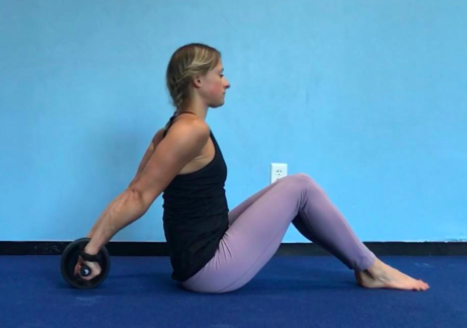 Reviewer uses black ab roller to work on their core and shoulder muscles on a floor