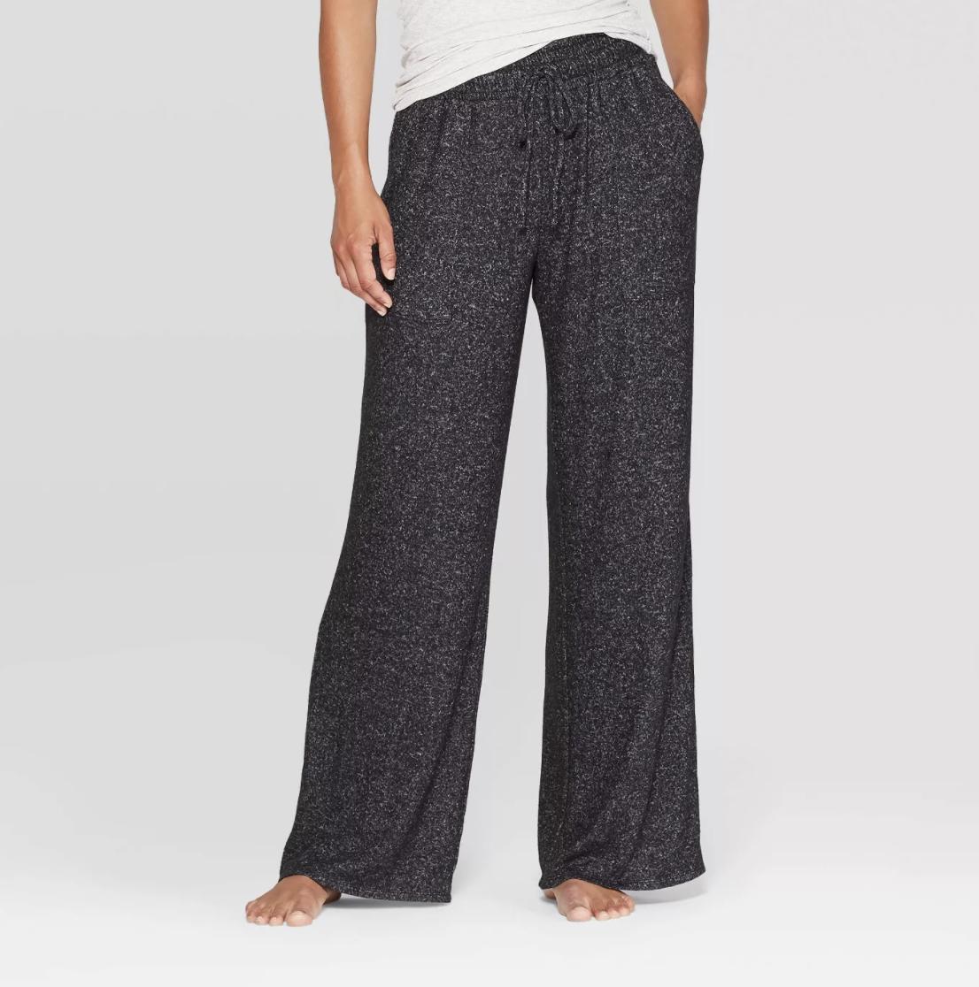 a model wearing grey speckled long pants