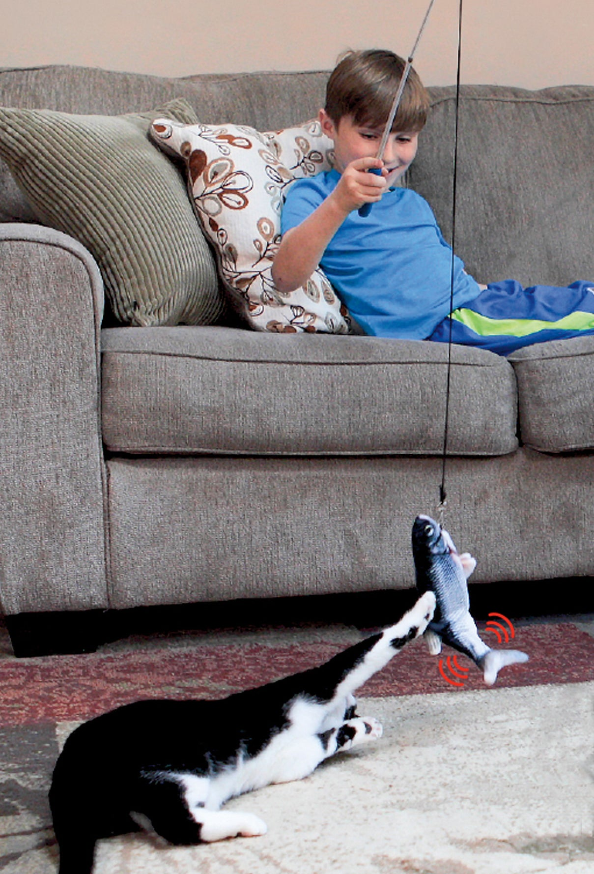 kid using a fishing pole to tease cat with flippity fish toy