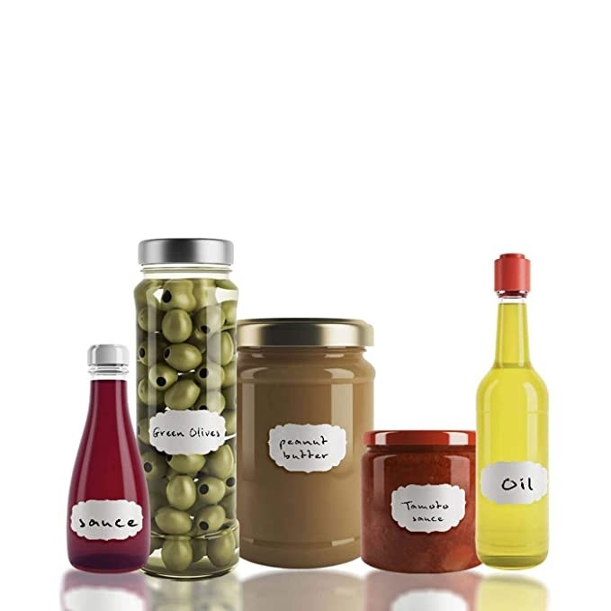 Bottles and jars of olives, oil, peanut butter and sauce labelled with the stickers.