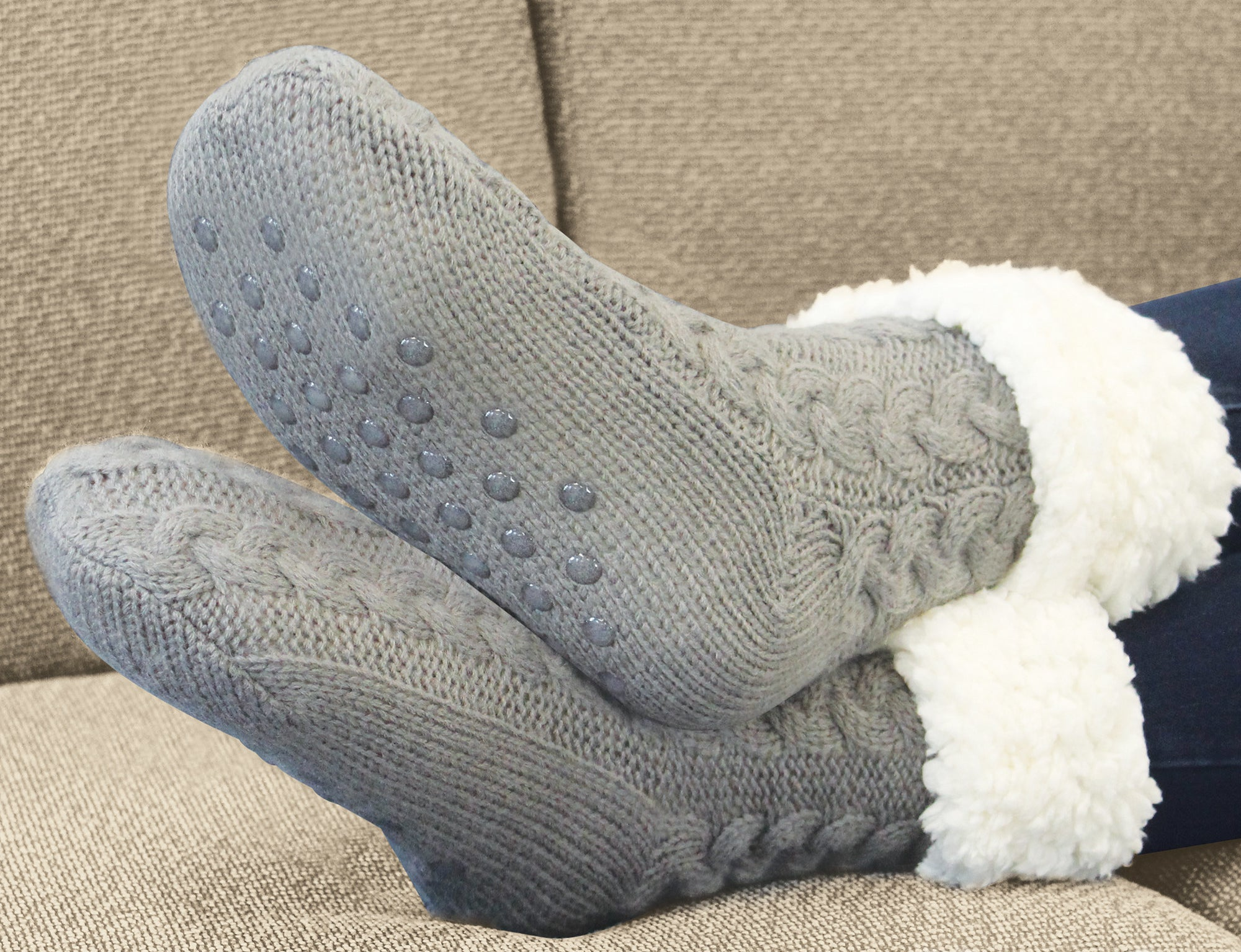 person wearing grey huggle socks while lounging on the couch