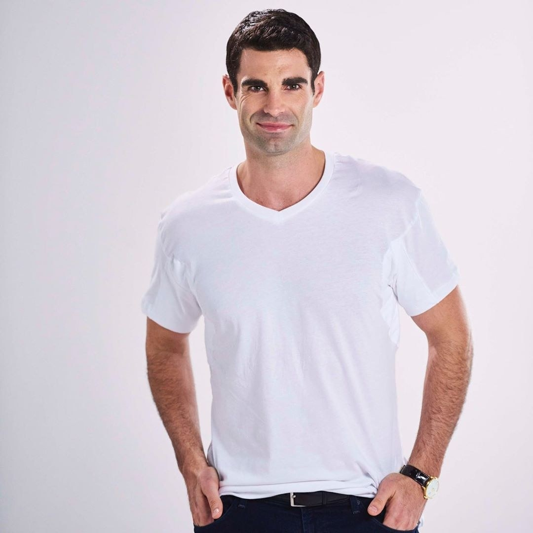 A person wearing a slim fitting T-shirt and jeans