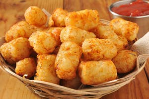 A basket of golden tater tots with a side of ketchup
