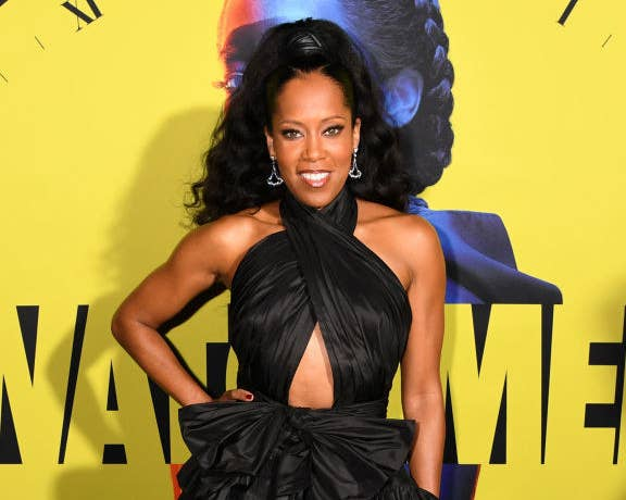 """Regina King posing in front of a """"Watchmen"""" poster"""