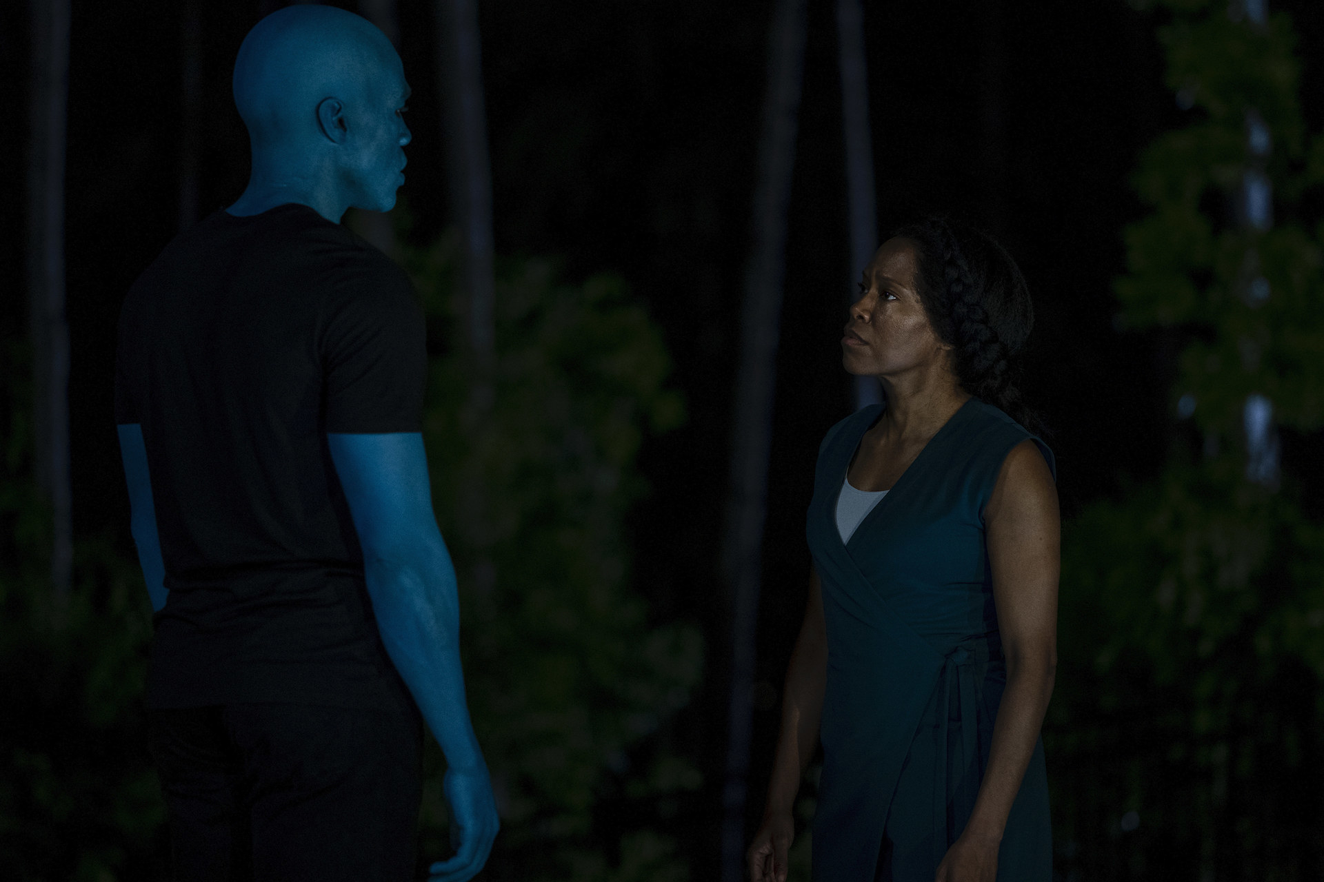 Yahya stands across from Regina King with blue skin as Doctor Manhattan in 'Watchmen'